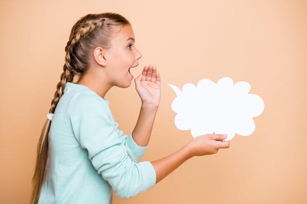 Photo de profil de belle petite dame excitée tenir nuage de papier vide disant dialogue chuchotant réponse main près de la bouche porter chandail bleu mur de couleur pastel beige isolé