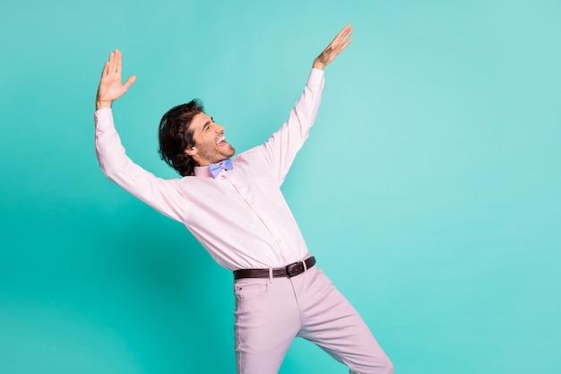 Photo de profil de charmant homme clubber cheveux bouclés brunet porter une chemise rose dansant qui s'étend des mains à côté de l'espace vide isolé sur fond de couleur sarcelle