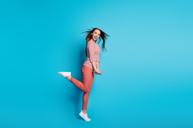 Photo de profil complet du corps d'une charmante femme insouciante profiter de la coupe de cheveux coupe de cheveux coup de vent temps libre le week-end porter des vêtements de style décontracté blanc gumshoes fond de couleur bleu isolé