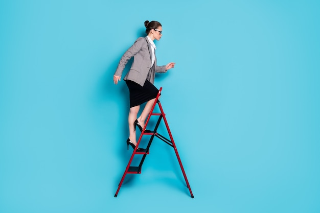 Photo de profil complet du corps d'une dame ambitieuse gravissant une échelle de carrière porter une jupe de blazer isolée sur fond de couleur bleu