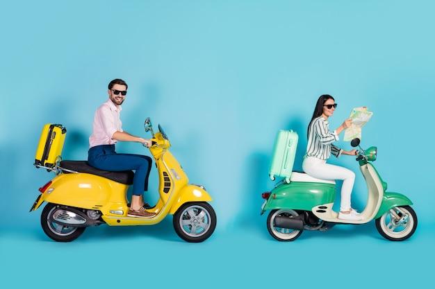 Photo de profil complet du corps de drôle de dame guy conduire deux valises de cyclomoteur rétro fixées derrière les voyageurs accros utilisent une carte papier pour l'orientation des vêtements de soirée isolé mur de couleur bleu