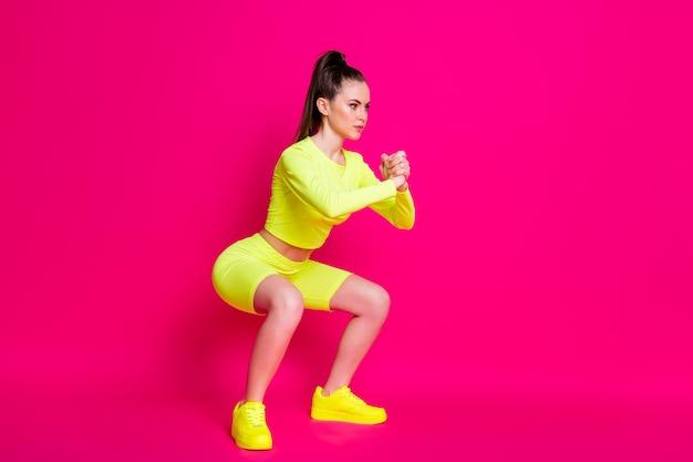 Photo de profil complet du corps d'une fille athlétique intense faisant des redressements assis isolés sur fond de couleur rose vif
