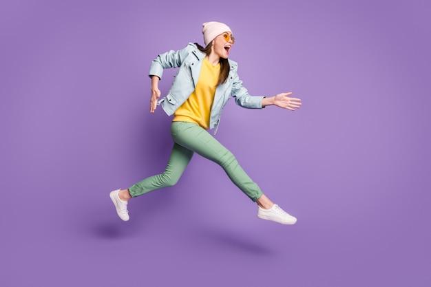 Photo de profil complet du corps d'une fille joyeuse et choquée qui saute après que les remises portent un pantalon de couvre-chef vert jaune isolé sur fond de couleur violette