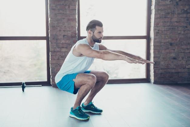 Photo de profil complet du corps d'un homme macho faisant des squats statiques processus de combustion des graisses vêtements de sport shorts de sport baskets maison d'entraînement près de grandes fenêtres à l'intérieur