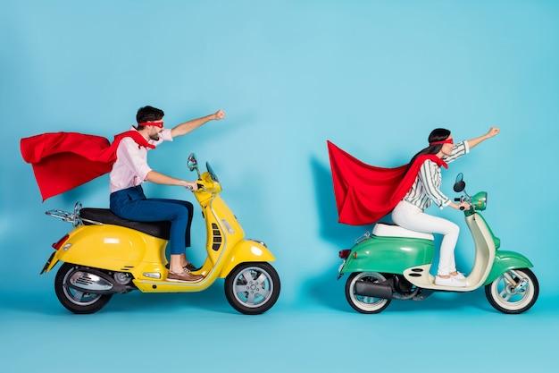 Photo de profil complet du corps d'un mec de dame folle conduire deux poings de levage de cyclomoteur vintage portent un masque de cape rouge se précipitant sur la route partie super héros manteau de rôle volant air isolé mur de couleur bleu