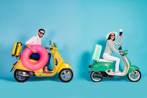 Photo de profil complet du corps de mec drôle de dame deux personnes conduisent des valises de cyclomoteur rétro montrer des billets transporter cercle gonflable rose tenue de cérémonie chapeau de soleil spécifications mur de couleur bleu isolé