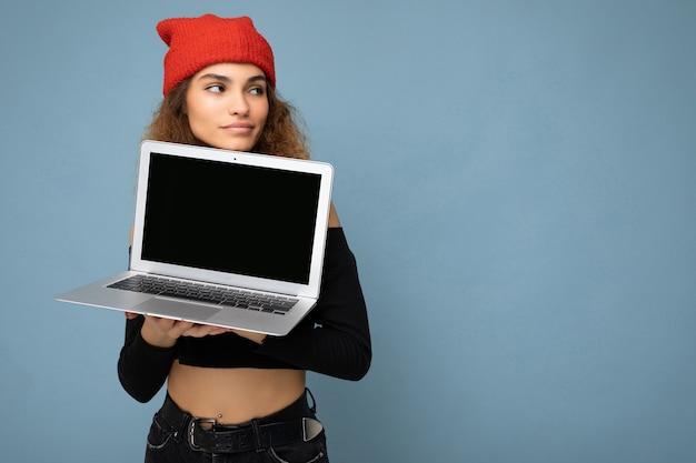 Photo de profil de côté tourné de beautify drôle heureux jeune brunet bouclés adolescente vêtue d'un crop top noir et rouge et orange do-rag isolé sur fond de mur bleu clair tenant un ordinateur portable wi