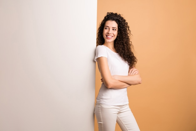 Photo de profil de drôle de dame debout confiant grande pancarte blanche présentant des informations de nouveauté promoteur porter des vêtements blancs fond de couleur pastel beige isolé
