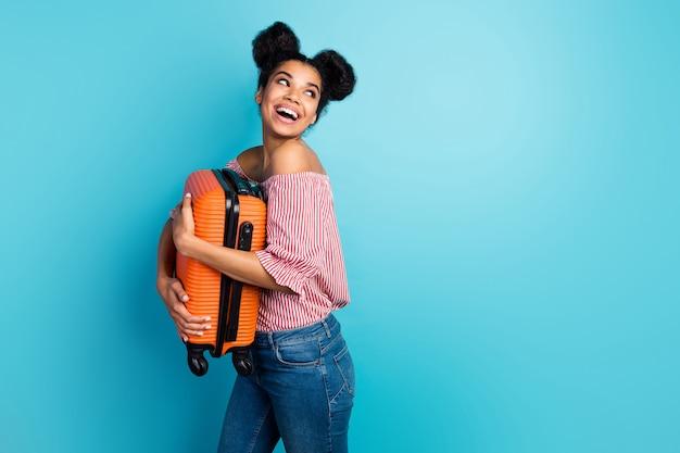 Photo de profil de drôle de jolie peau sombre dame tenir grosse valise lourde profiter de voyager regarder côté espace vide porter rayé rouge blanc hors-épaules chemisier jeans mur de couleur bleu