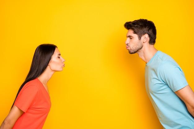 Photo de profil de drôle mignon deux personnes guy dame yeux fermés debout en face de bisous aveugles datant porter des t-shirts orange bleu décontracté mur de couleur jaune