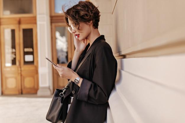 Photo de profil d'une femme cool aux cheveux courts en veste noire tient la tablette à l'extérieur. belle femme dans des lunettes avec sac à main posant dans la rue.