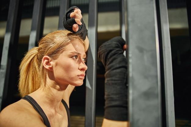 Photo de profil d'une femme en forme qui fait une pause entre les séances d'entraînement