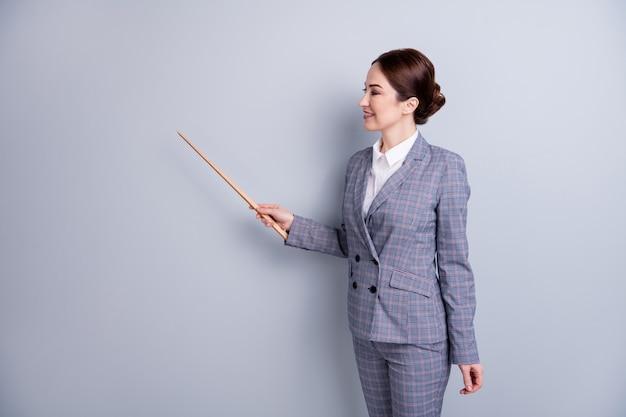 Photo de profil d'une femme séduisante, bonne humeur, occupation des enseignants, leçon en ligne sur internet, montrant le pointeur de l'espace vide, nouvel objet à thème porter un costume à carreaux isolé sur fond de couleur grise