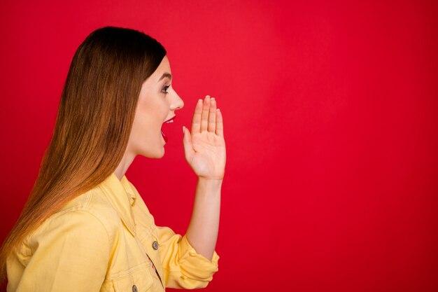 Photo de profil en gros plan d'une femme séduisante regarde côté espace vide criant partageant des informations sur les gens bras près de la bouche porter une veste de blazer en jean jaune décontractée isolée sur fond de couleur rouge vif