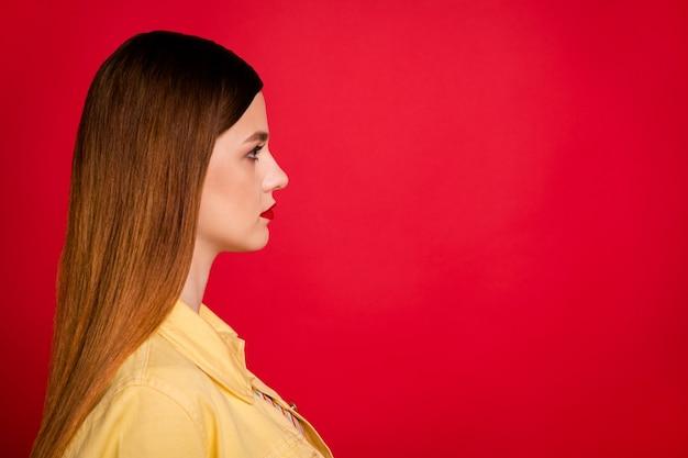 Photo de profil en gros plan d'une jolie dame séduisante pommade brillante côté espace vide intéressé pas souriant porter une veste de blazer en jean jaune décontractée isolée sur fond de couleur rouge vif