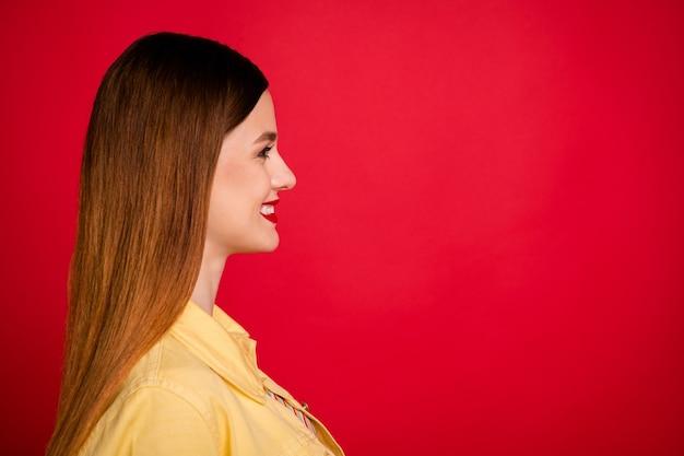 Photo de profil en gros plan d'une jolie dame séduisante pommade brillante côté espace vide intéressé souriant dents blanches porter une veste de blazer en jean jaune décontractée isolée sur fond de couleur rouge vif