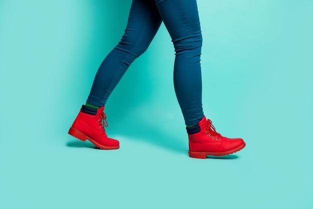 Photo de profil gros plan recadrée de fit dame jambes hanches marchant vers le bas à l'étranger rue pays étranger porter des chaussures rouges élégantes pantalons mur de couleur sarcelle isolé