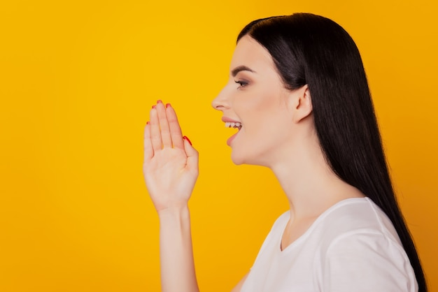 Photo de profil de jeune femme séduisante les mains près de la bouche disent dire aux nouvelles crier annonce isolée sur fond de couleur jaune