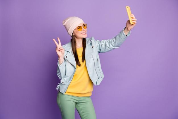 Photo de profil d'une jolie dame élégante tenant un téléphone souriant montrant des symboles de signe v faisant des selfies portant des spécifications de soleil chapeau décontracté veste bleue pull pantalon vert fond de couleur violet isolé