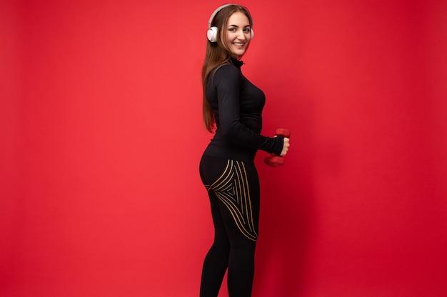 Photo de profil d'une jolie jeune femme brune souriante et positive portant des vêtements de sport noirs