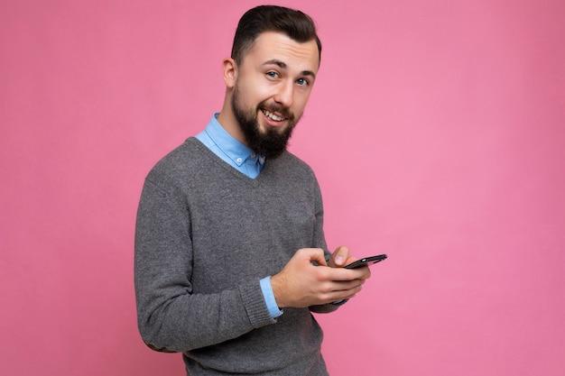 Photo de profil latéral d'un beau jeune homme non rasé brunet avec une barbe vêtue de gris