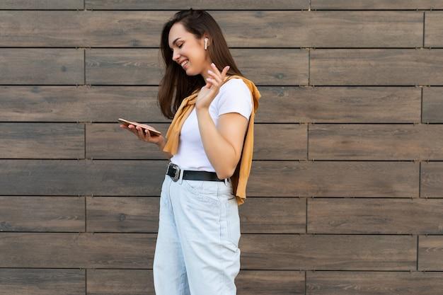 Photo de profil latéral d'une belle jeune femme brune heureuse portant des vêtements décontractés et écoutant de la musique via des écouteurs sans fil, debout dans la rue, tenant et utilisant un téléphone portable en regardant l'écran