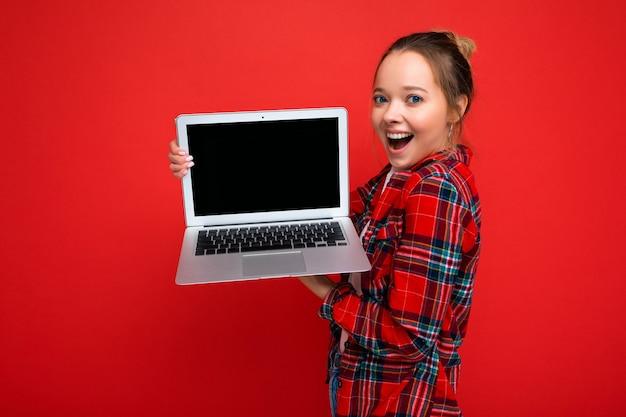 Photo de profil latéral d'une charmante jeune femme surprise assez étonnée tenant un ordinateur portable portant une chemise rouge