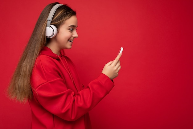 Photo de profil latéral d'une jolie fille brune souriante et positive portant un sweat à capuche rouge isolé sur rouge