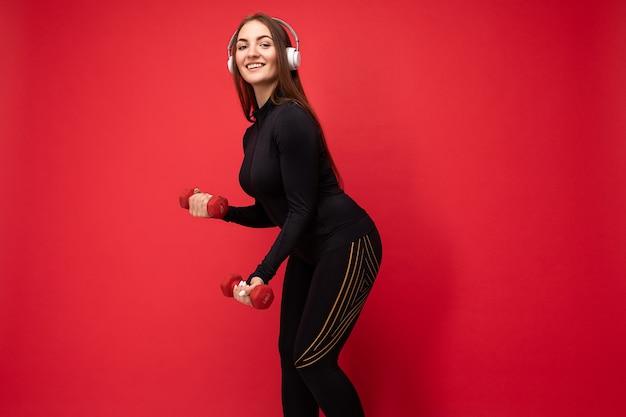 Photo de profil latéral de jolie jeune femme brune souriante positive portant des vêtements de sport noirs