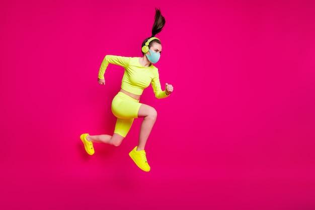 Photo de profil latéral de la taille du corps sur toute la longueur d'une sportive sautant en hauteur en courant rapide portant un masque isolé sur fond de couleur fuchsia vif