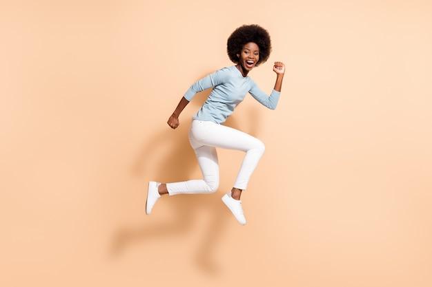 Photo de profil latéral sur toute la longueur du corps d'une drôle de fille bouclée à la peau foncée sautant haut en courant rapidement en riant fort isolée sur fond de couleur beige