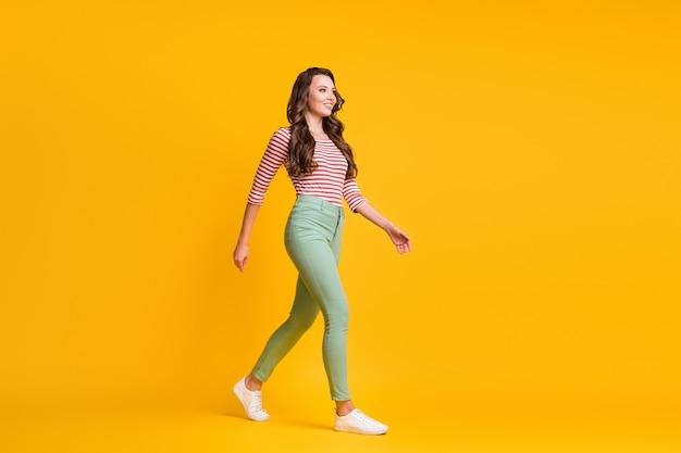 Photo de profil latéral sur toute la longueur du corps d'une fille aux cheveux bouclés allant vite souriant isolée sur fond de couleur jaune vif
