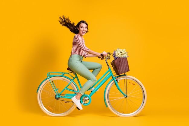 Photo de profil latéral sur toute la longueur du corps d'une fille joyeuse faisant du vélo bleu avec un panier de fleurs isolé sur un fond de couleur jaune vif