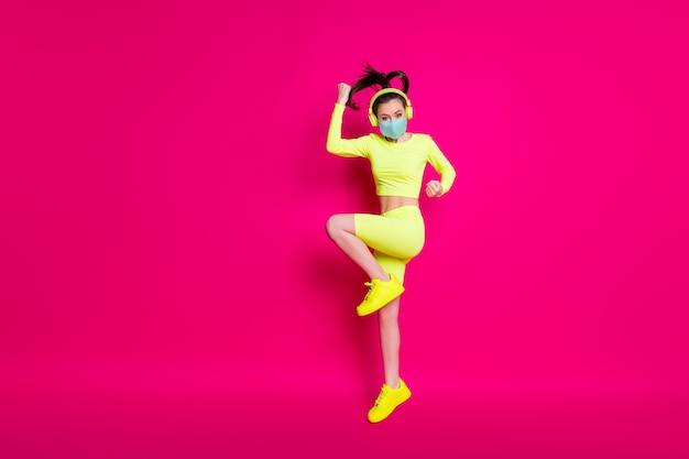 Photo de profil latéral sur toute la longueur du corps d'une sportive sautant en train d'écouter de la musique isolée sur fond de couleur fuchsia vif