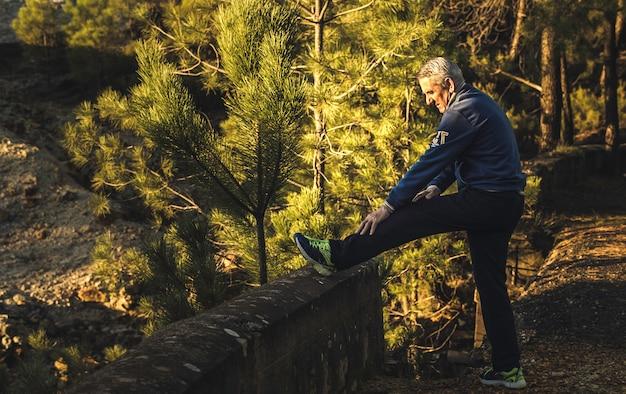 Photo de profil d'une personne âgée aux cheveux blancs dans un vêtement de sport faisant des exercices