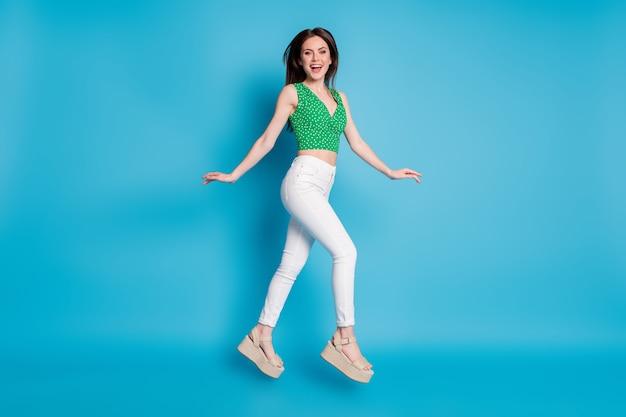Photo de profil pleine grandeur d'une belle fille énergique qui saute à pied aller copyspace profitez du week-end porter des vêtements de bonne apparence isolés sur fond de couleur bleue