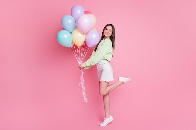Photo de profil pleine grandeur de la charmante dame fête d'anniversaire meilleur ami invité tenir des ballons à air félicitations porter décontracté vert pull pull jeans mini jupe isolé fond de couleur pastel rose
