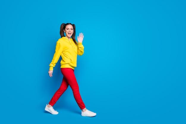 Photo de profil pleine grandeur d'une dame joyeuse à deux queues, bonne humeur, rue à pied voir des amis agitant la main porter des vêtements décontractés à capuche jaune pull pantalon rouge baskets isolées fond de couleur bleu vif