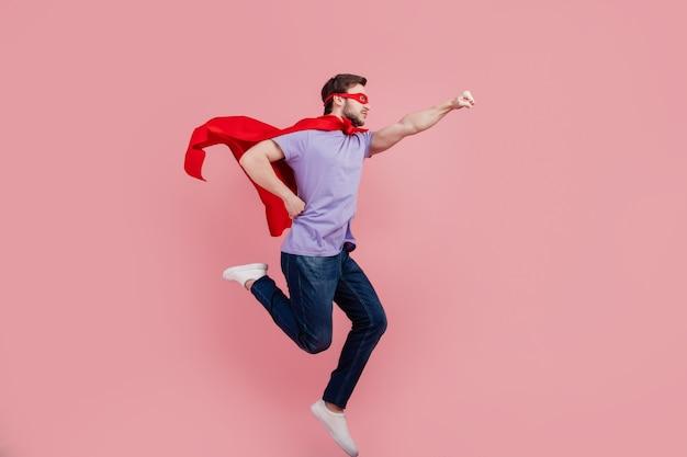 Photo de profil pleine grandeur du jeune superman aide à la course de sécurité à forte puissance isolée sur fond de couleur rose