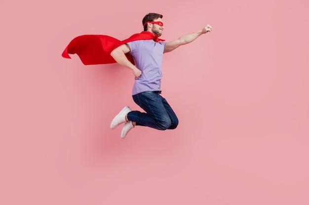 Photo de profil pleine grandeur du jeune superman de la sécurité à forte puissance de saut prêt à aider isolé sur fond de couleur rose
