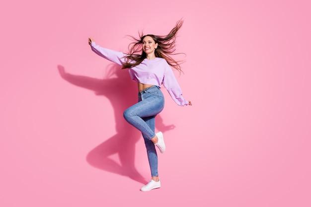 Photo de profil pleine grandeur d'une fille franche et satisfaite profiter du temps libre pour lever la main porter des vêtements de bonne humeur coupe de cheveux air vent isolé fond de couleur rose
