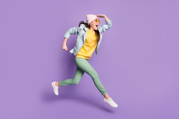 Photo de profil pleine grandeur d'une fille joyeuse excitée voir découvrir une incroyable remise de saut courir rapidement porter des chapeaux pantalons verts pantalons veste en cuir isolé fond de couleur violet