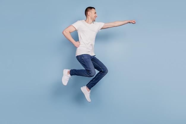 Photo de profil pleine grandeur d'un homme excité sautant sur un super-héros aérien isolé sur fond de couleur bleu