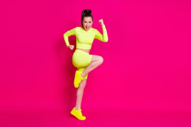 Photo de profil pleine grandeur d'une jeune femme étonnée debout poings levés crier des baskets de costume de sport isolées sur fond de couleur rose
