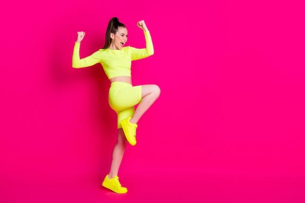 Photo de profil pleine grandeur d'une jeune femme étonnée debout poings levés crier look espace vide costume de sport isolé sur fond de couleur rose