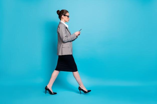 Photo de profil pleine grandeur lady boss go copyspace utiliser cellphone wear blazers jupe isolé fond de couleur bleu