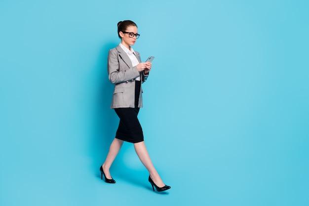Photo de profil pleine longueur boss girl go utiliser jupe veste veste d'usure smartphone isolé fond de couleur bleu