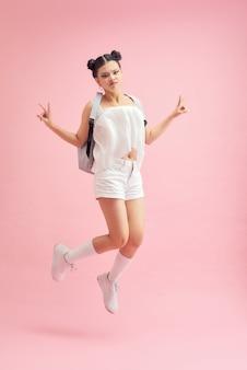 Photo de profil pleine longueur d'une étudiante drôle sautant haut montrant des symboles v-sign porter un sac isolé sur fond de couleur rose