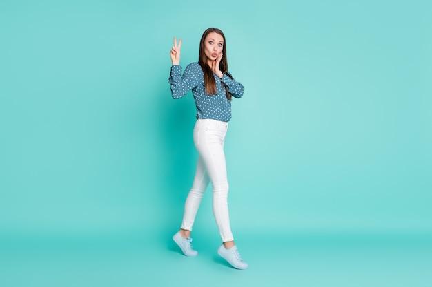 Photo de profil pleine longueur d'une fille étonnée aller regarder à huis clos faire v-sign isolé sur fond de couleur turquoise