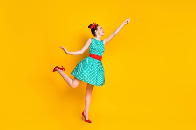 Photo de profil pleine longueur d'une fille gaie tenir la main de fond porter une tenue sarcelle isolée sur un fond de couleur vive